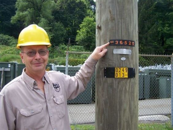 Lineman pointing to Power Pole Identification Number